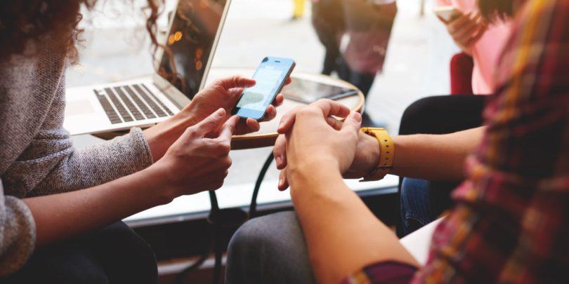 dvieju zmoniu rankos, kompiuteris, ismanusis telefonas rankose